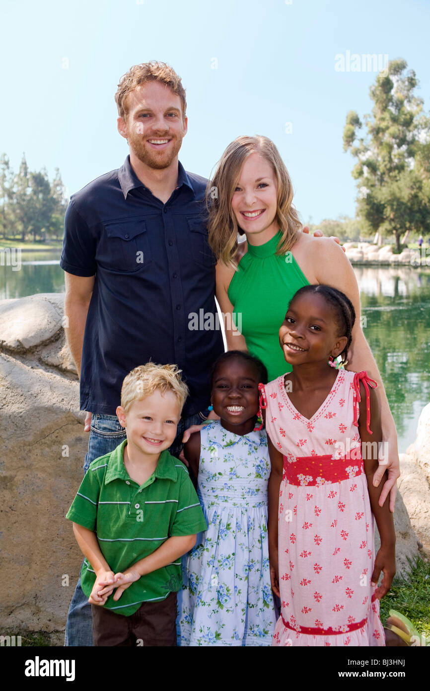 ethnic multi racial racially diverse multicultural multi cultural Young couple with son adoption West African siblings - Stock Image