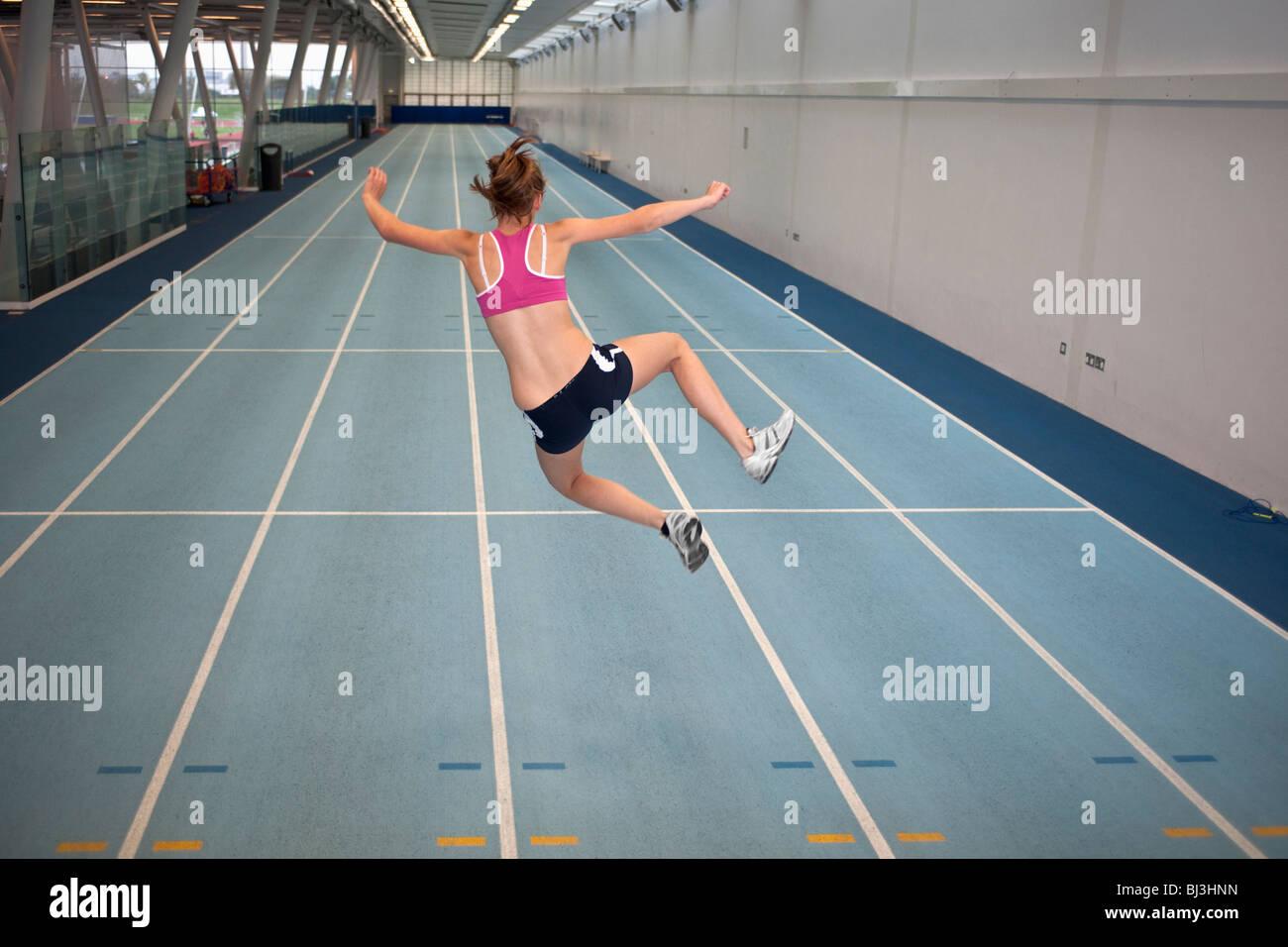 female athlete doing crazy star jump - Stock Image