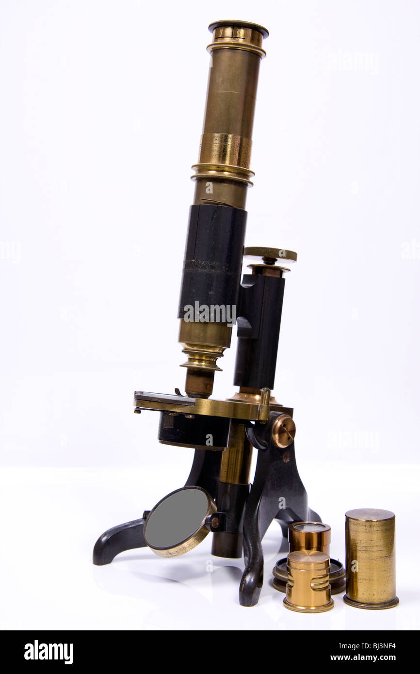 Antique Brass microscope with extra lenses against a white background - Stock Image