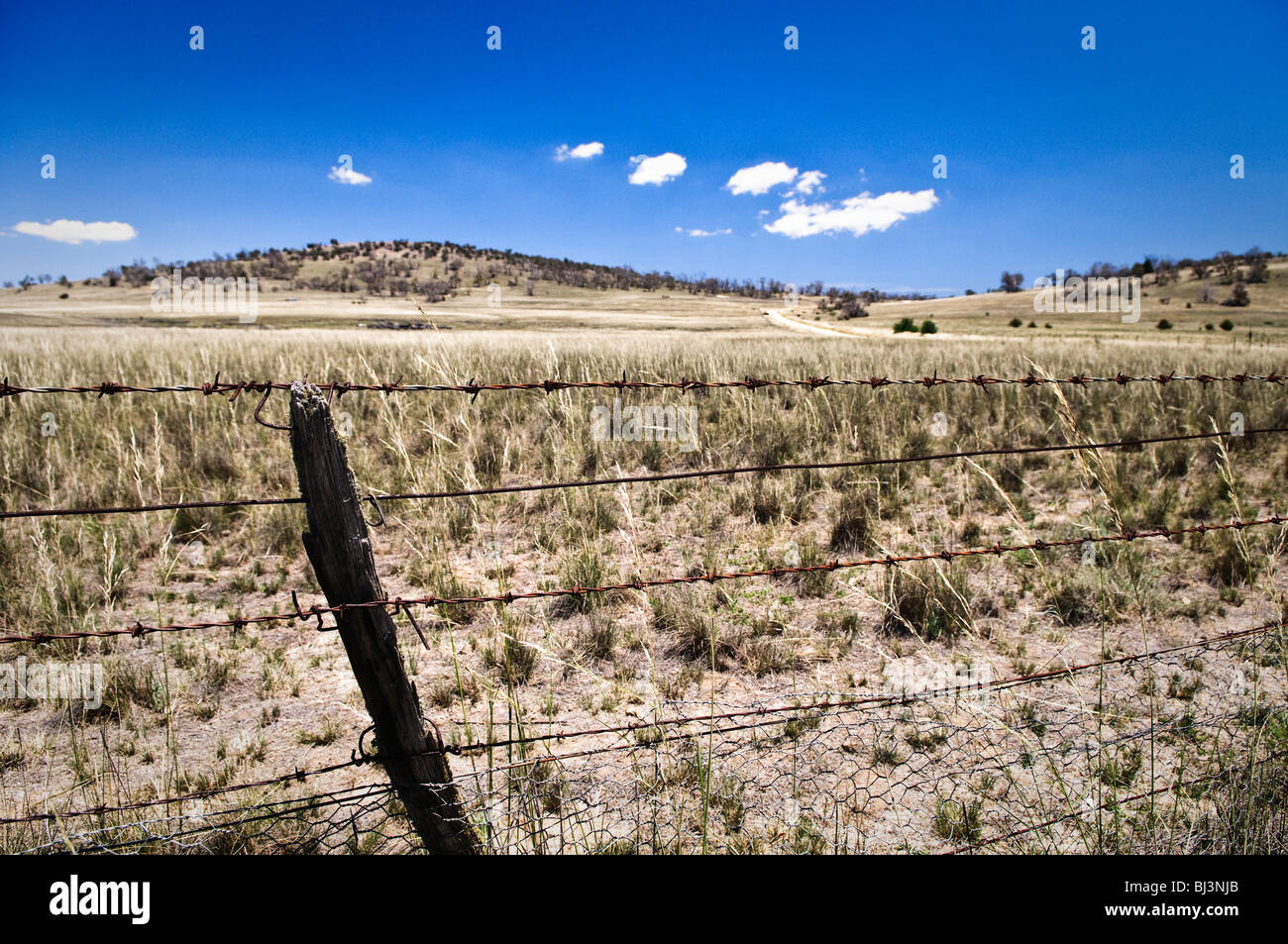 A barbed wire fence around a farm in drought in the Australian outback - Stock Image