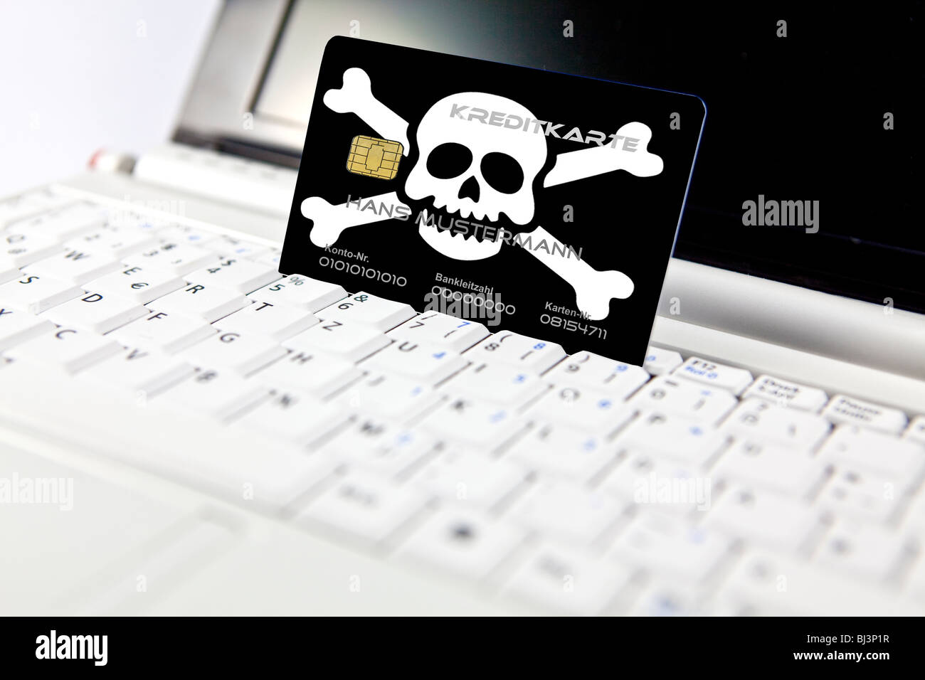 Credit card with a skull at a PC, notebook, symbolic image for the risk of data misuse when online shopping, data Stock Photo