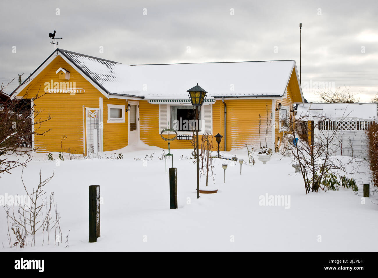 Yellow wooden house in a snow covered allotment garden, Denmark, Europe - Stock Image