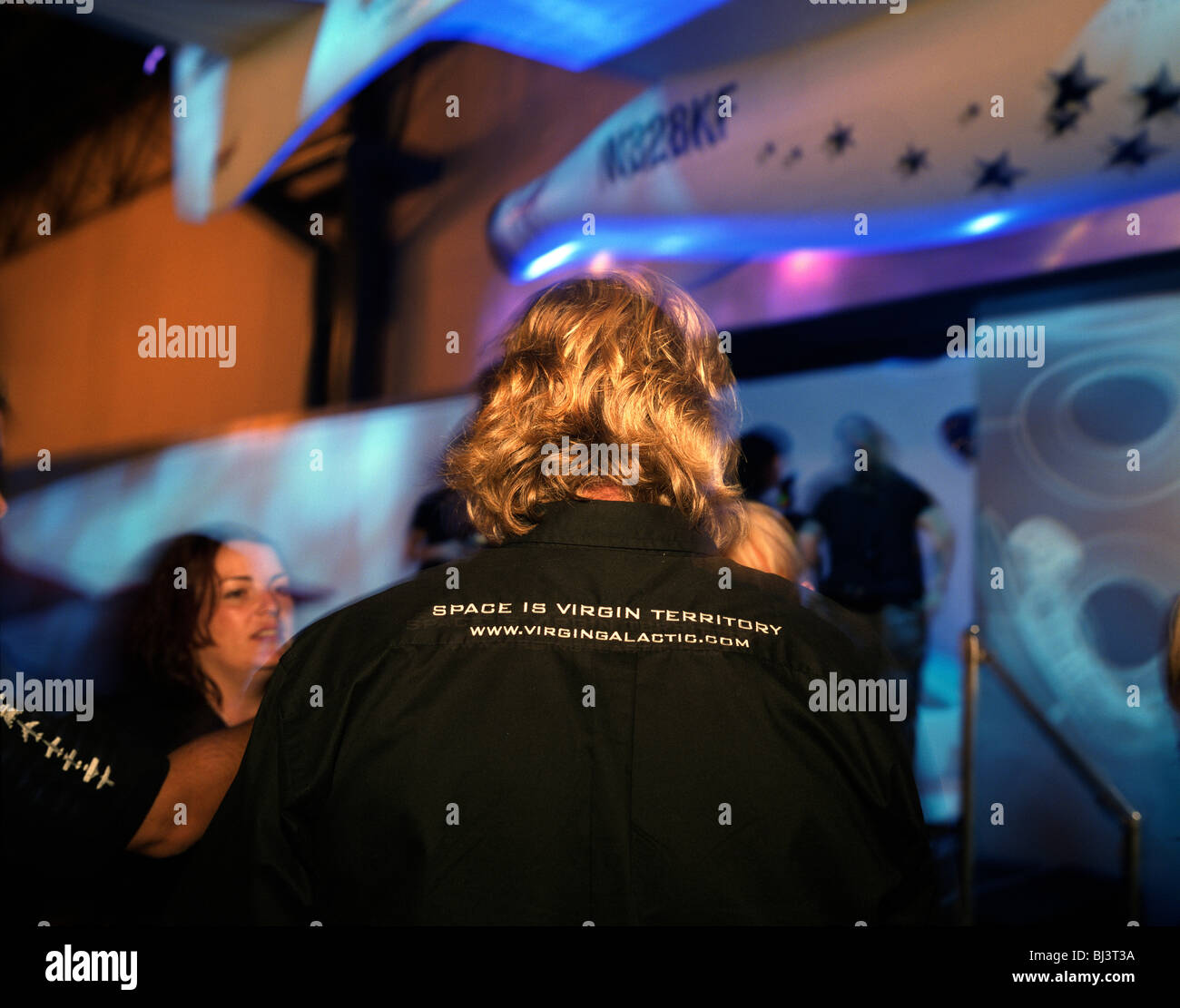 The back of greying-blonde head belonging to Sir Richard Branson of Virgin Galactic during SpaceShipTwo's replica - Stock Image
