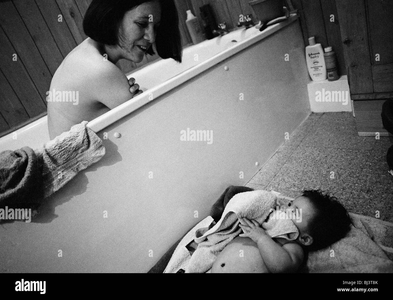 A mother peers over the bath to keep watch over her five month-old baby daughter who is lying on a matt. - Stock Image