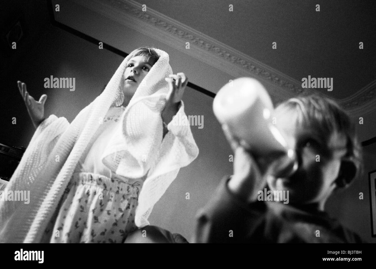 A four year-old girl plays some sort of religious role-play game - perhaps an angel or the Virgin Mary with her - Stock Image