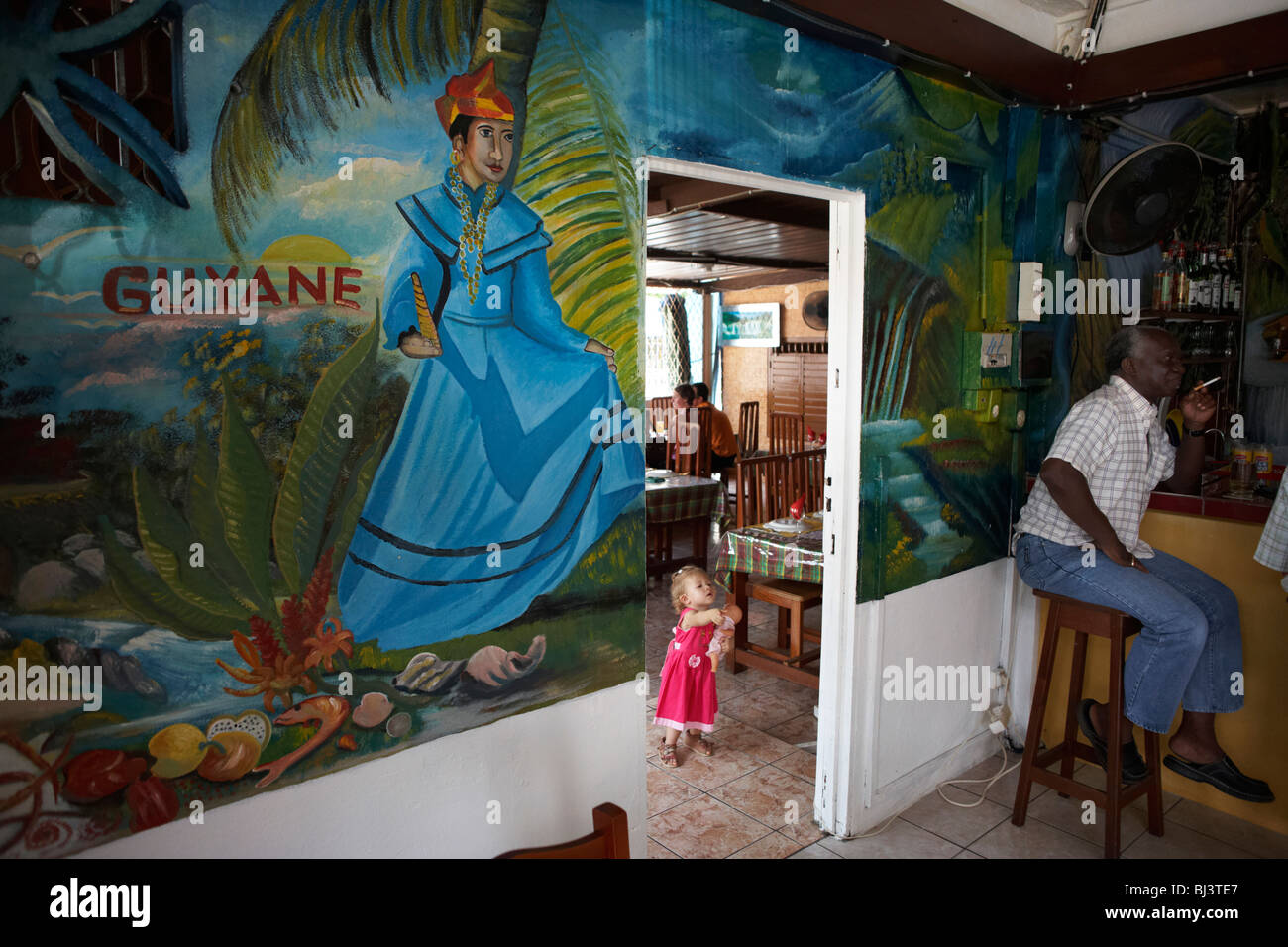 Holding her doll, a young white child wearing a pink dress explores the Délice Restaurant in old Kourou, French - Stock Image