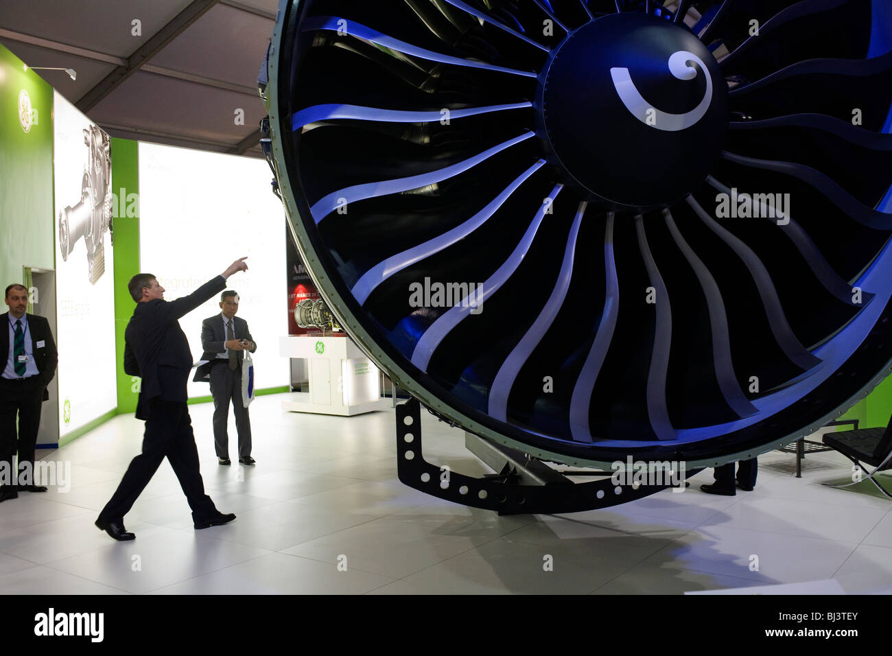 A visitor to the General Electric exhibition stand points to a feature on a massive, GE90-115B turbofan jet engine. - Stock Image
