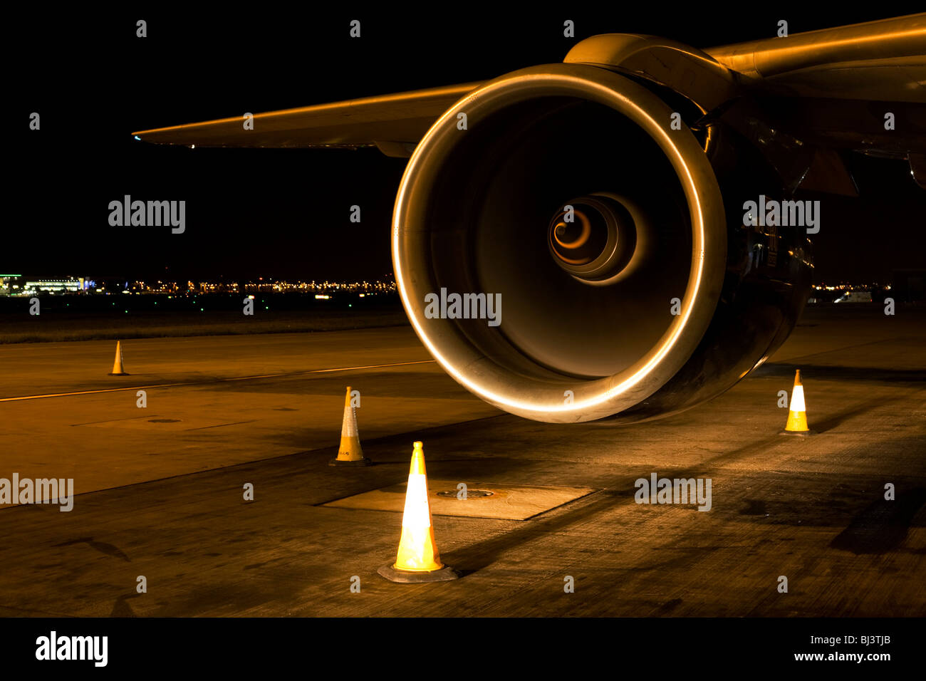British Airways Boeing jet aircraft engine highlighted by headlights of an Heathrow airfield vehicle. - Stock Image