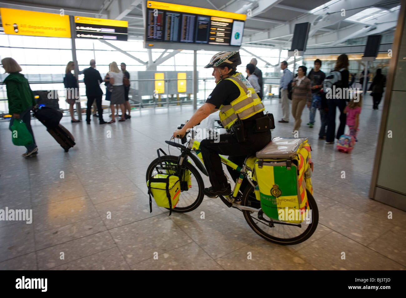 NHS Paramedic Janet Greenhead cycles through the departures concourse on her Specialized Rockhopper mountain bike - Stock Image
