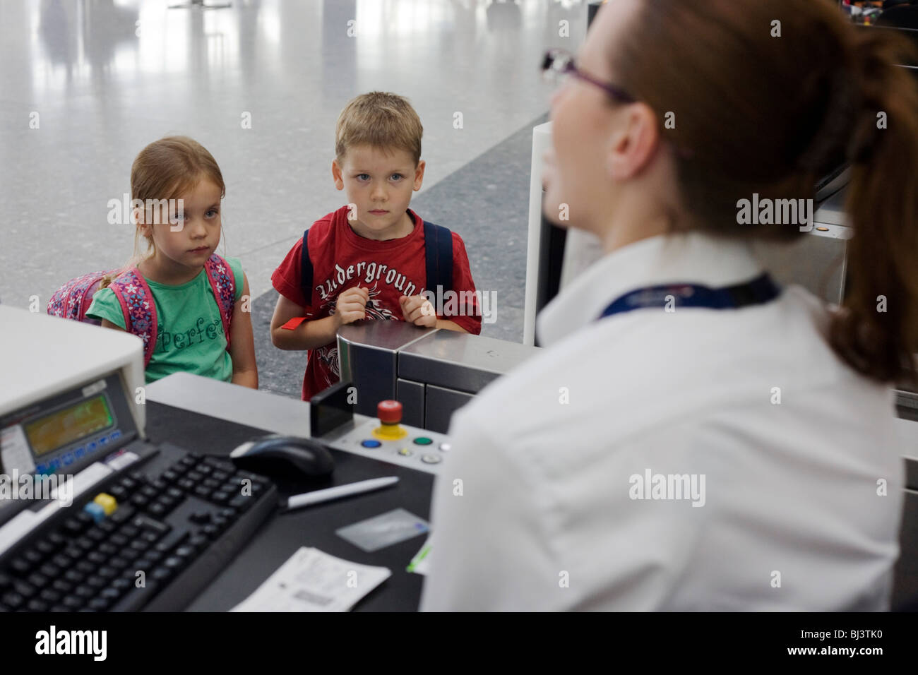 Young brother and sister look on in awe while a British Airways check-in lady asks security questions. - Stock Image