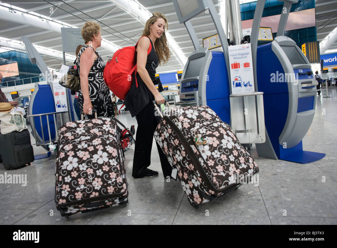 Two lady passengers haul matching suitcases at the British Airways self-check-in kiosk at Heathrow Airport's - Stock Image