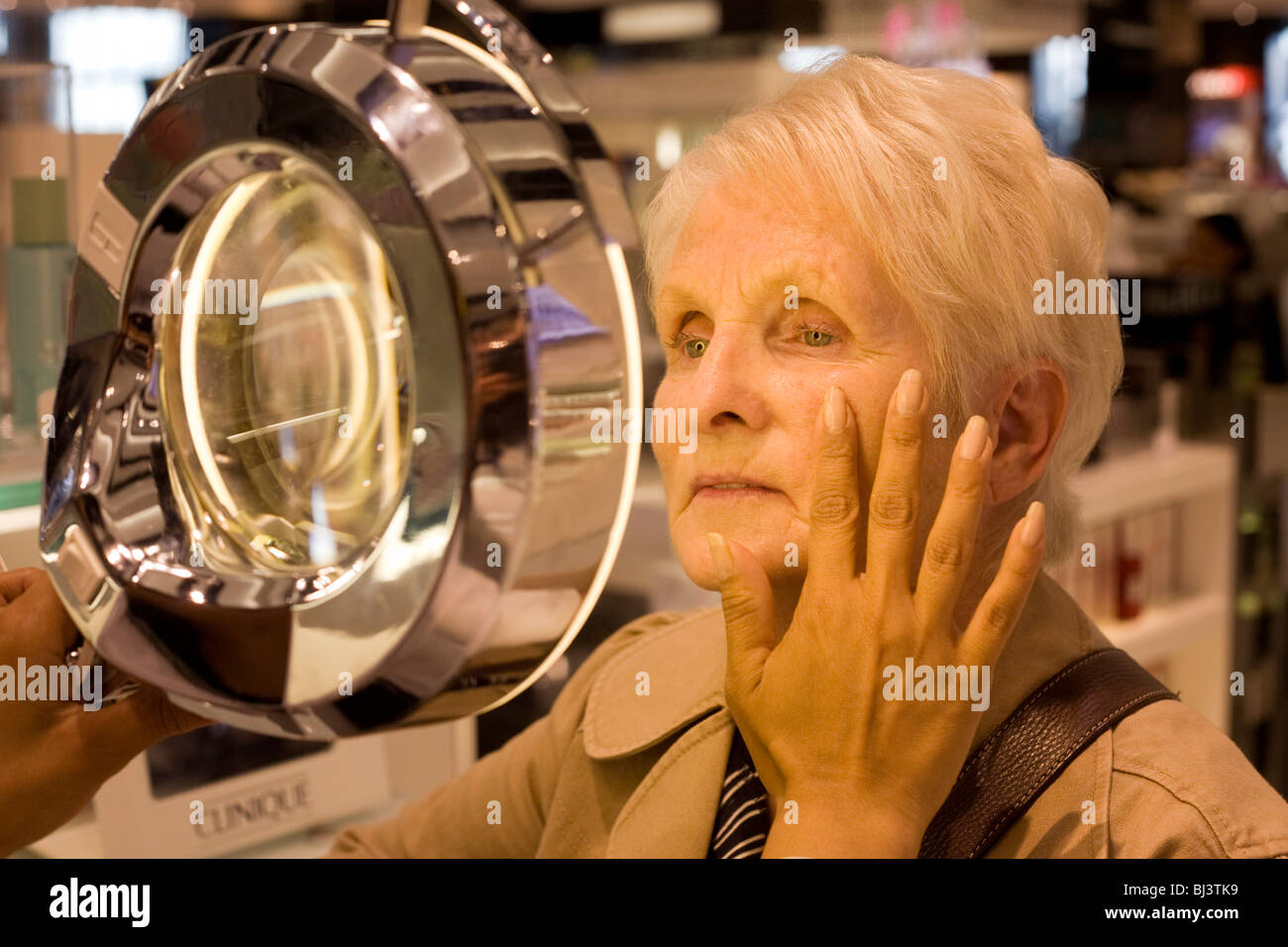 Elderly lady receives a consultation from professional beautician in the Clinique Bar at World Duty Free in Heathrow - Stock Image