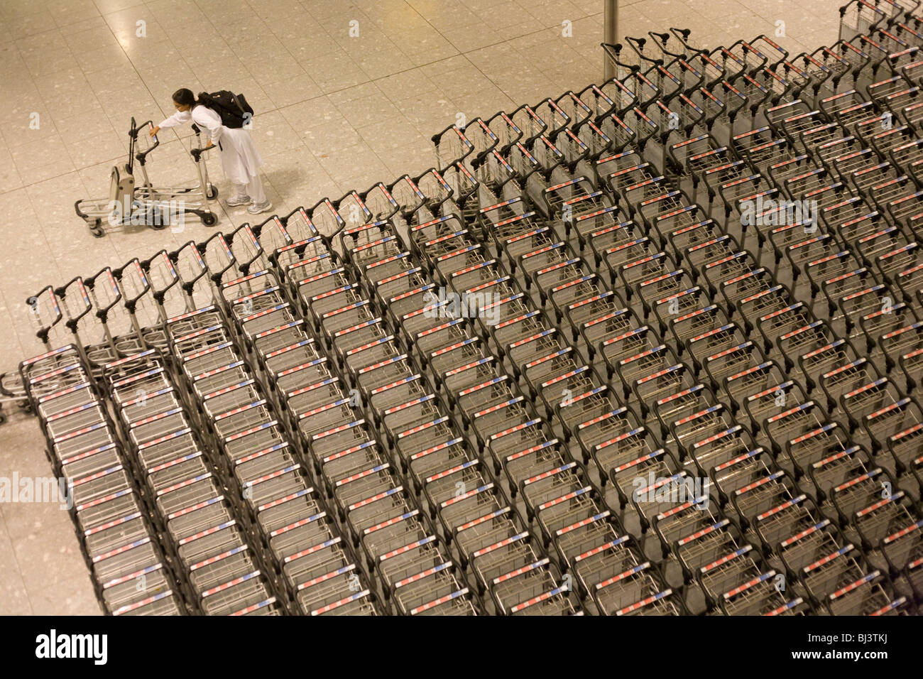 Airline passengers struggles to separate two trolleys in the baggage reclaim hall in the arrivals of Heathrow Airport. - Stock Image