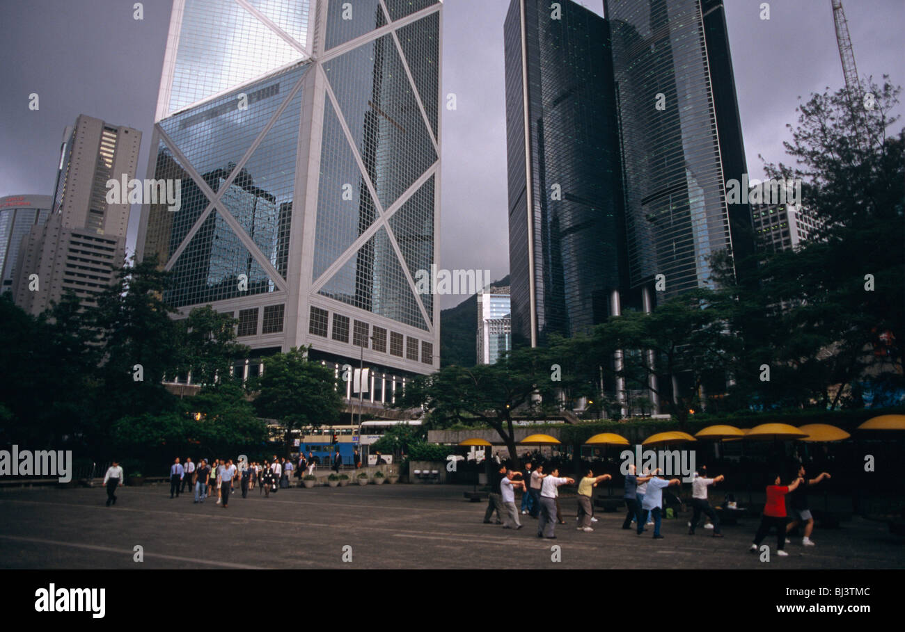 Commuters and exercise class beneath skyscrapers on the very last day of British rule over its Hong Kong colony. - Stock Image