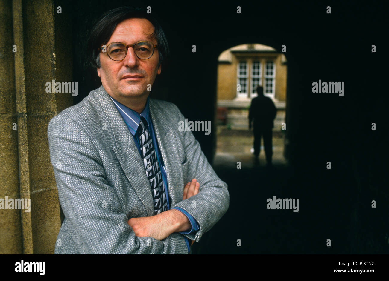 Political scientist John Gray, stands in doorway wearing  grey jacket and round-frame glasses in Quadrangle of Jesus - Stock Image