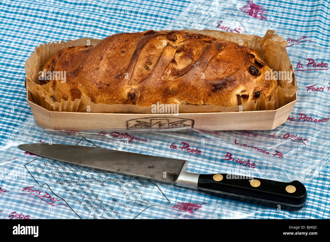 French Fig loaf in wrapper on breadboard. - Stock Image