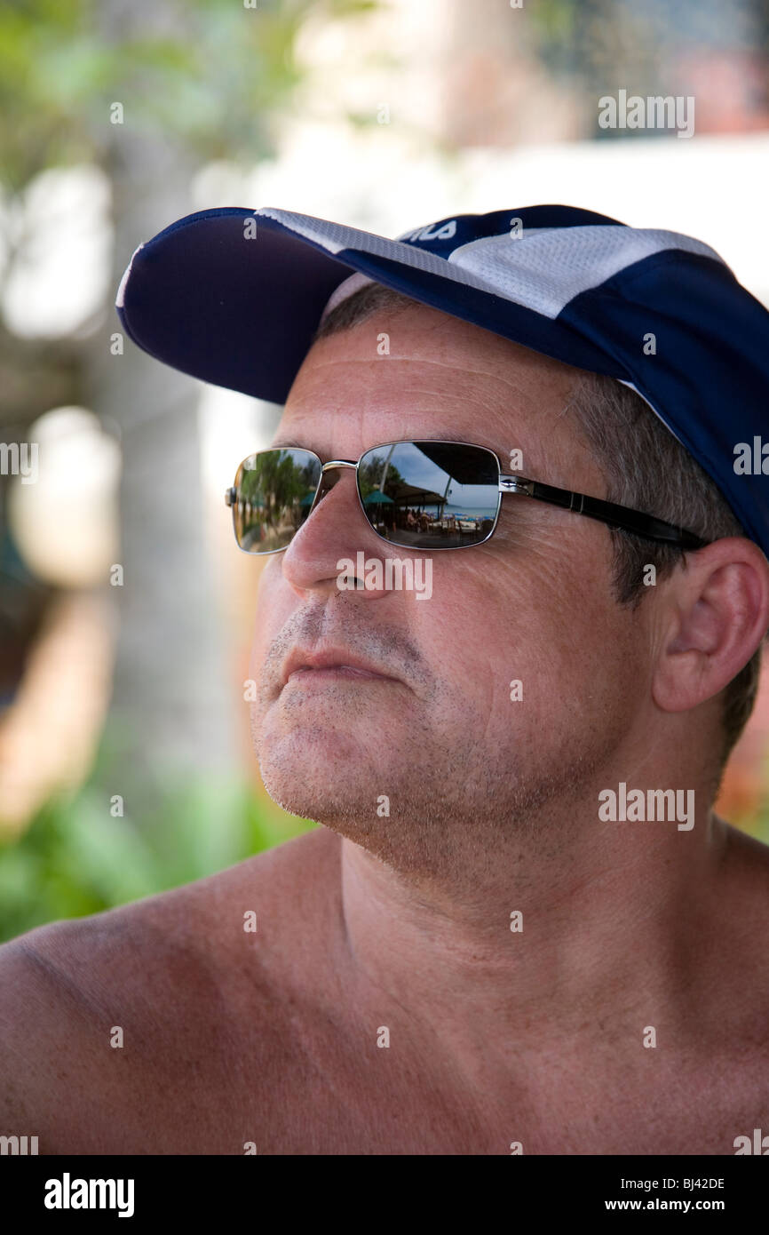 Man with peak cap and sunglasses - Stock Image