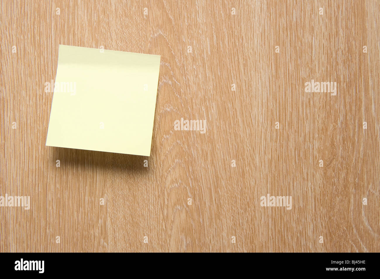 A Blank Yellow Postit Note on a Wooden Door - Stock Image