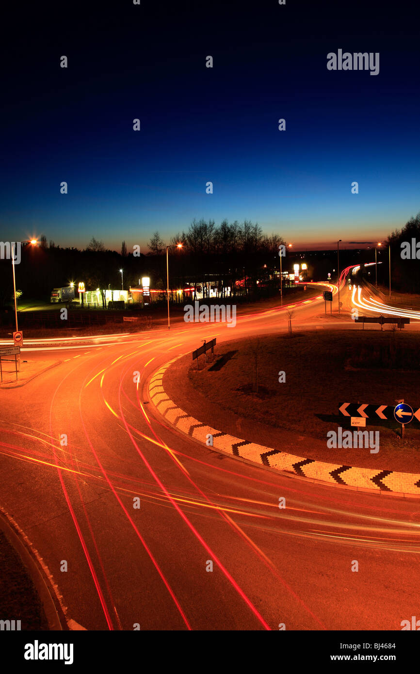 Cars and traffic light trails on a roundabout - Stock Image