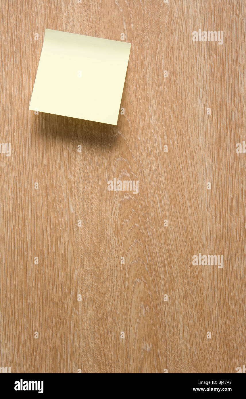 A Blank Yellow Post It Note on a Wooden Door - Stock Image