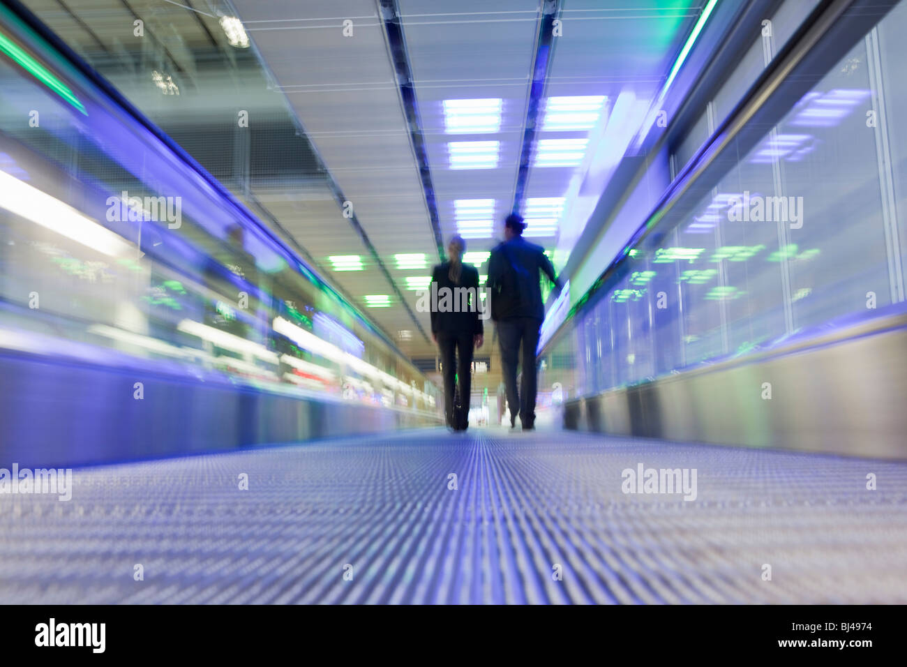conveyor belt with couple in background - Stock Image