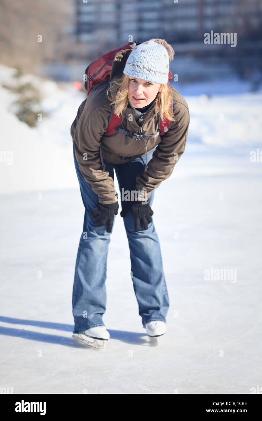 Tired woman ice skater on the Assiniboine River Trail, Winnipeg, Manitoba, Canada. - Stock Image