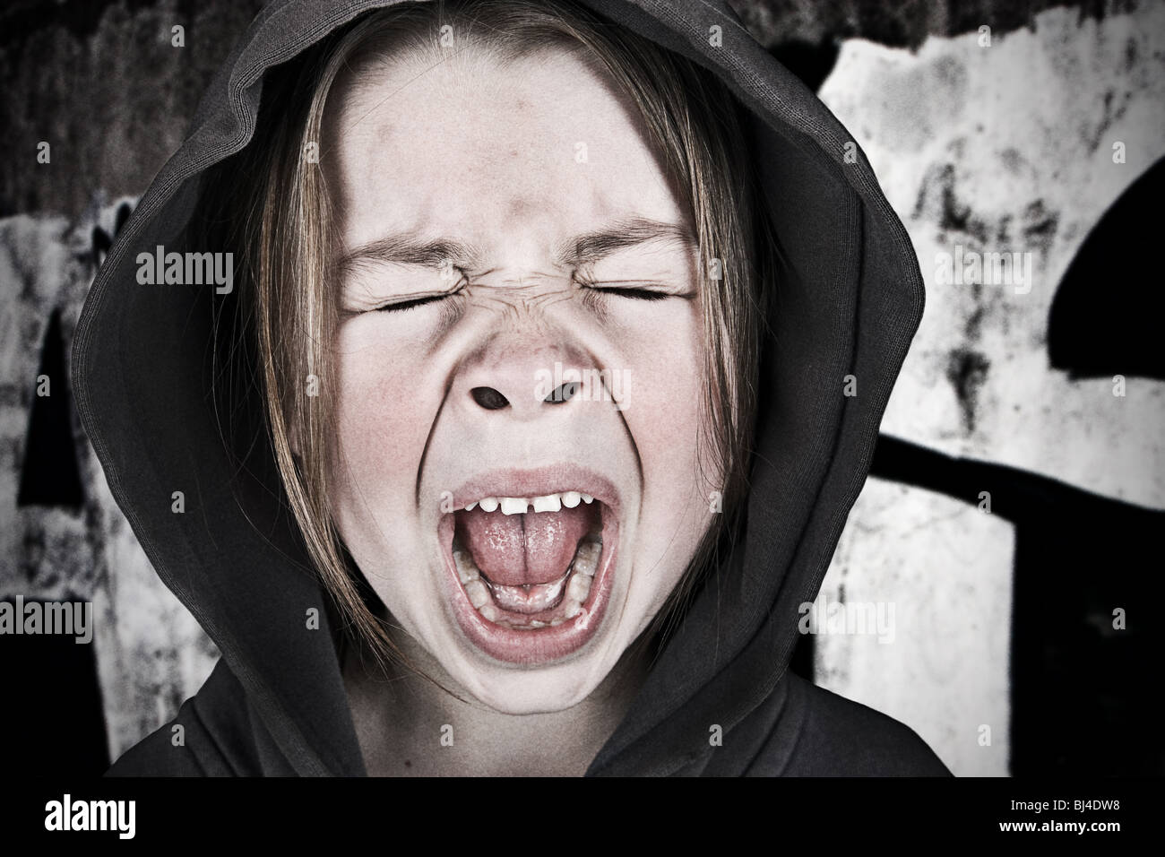 Shot of a Cute Girl in a Hooded Top Screaming - Stock Image