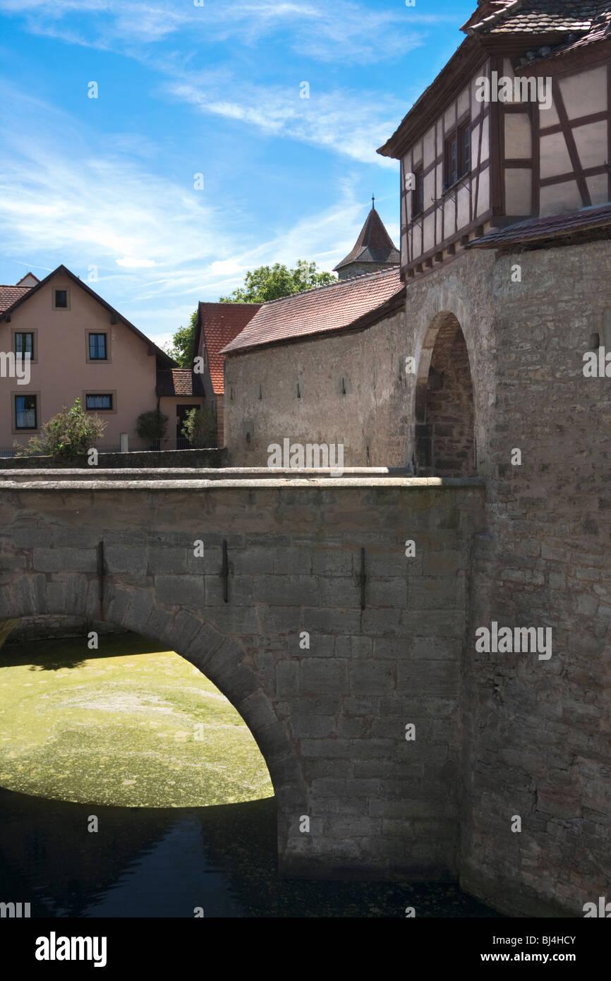 Bridge with moat leading into building, Rothenburg Ob Der Tauber, Hesse, Germany - Stock Image