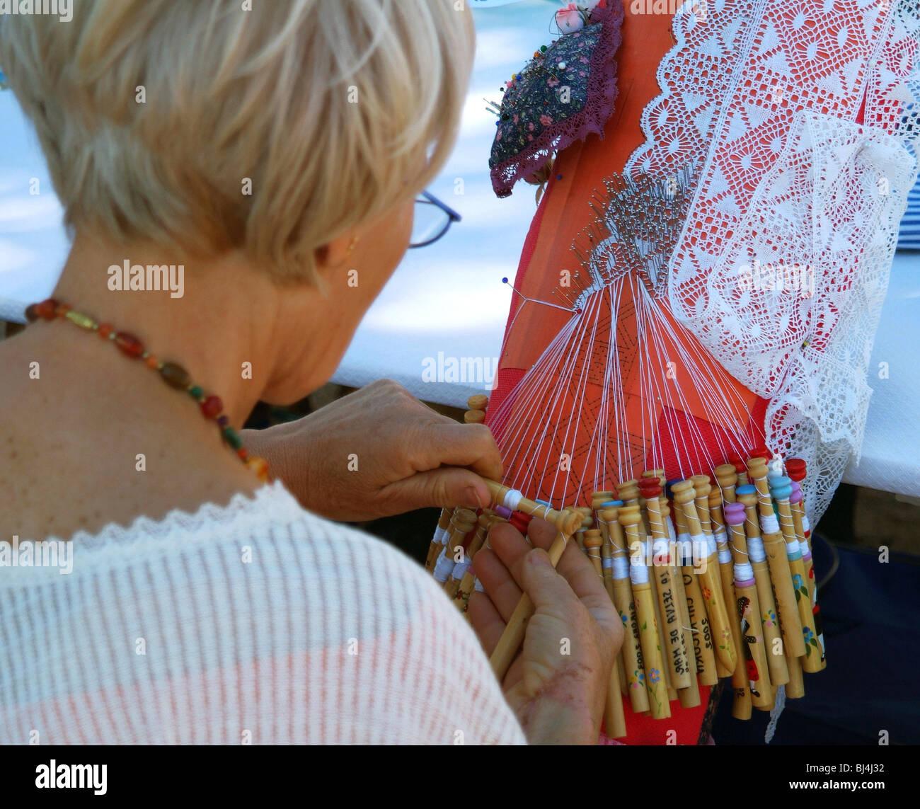 Woman making bobbin lace. - Stock Image