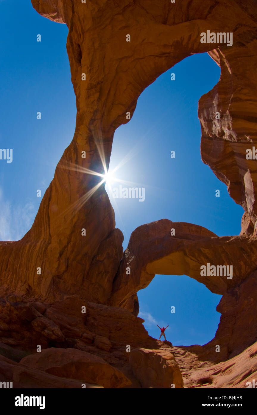 A hiker exults in the sun below Double Arch, Arches National Park, Utah - Stock Image
