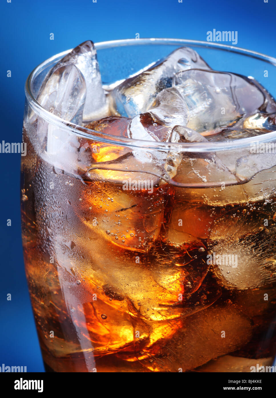 Glass of ice cola on a blue background - Stock Image