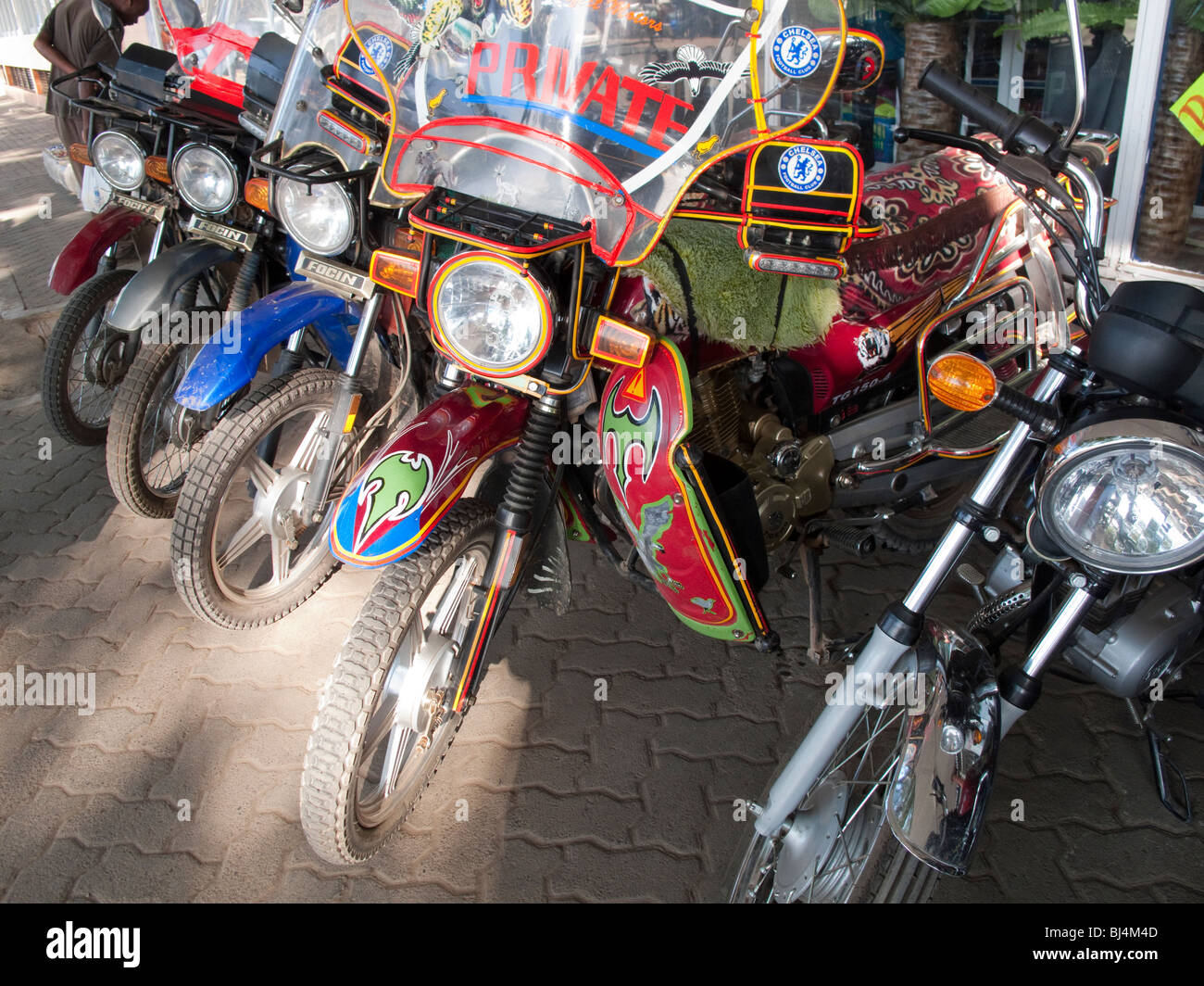 Decorated motorbikes parked in small town Kenya East Africa Stock Photo