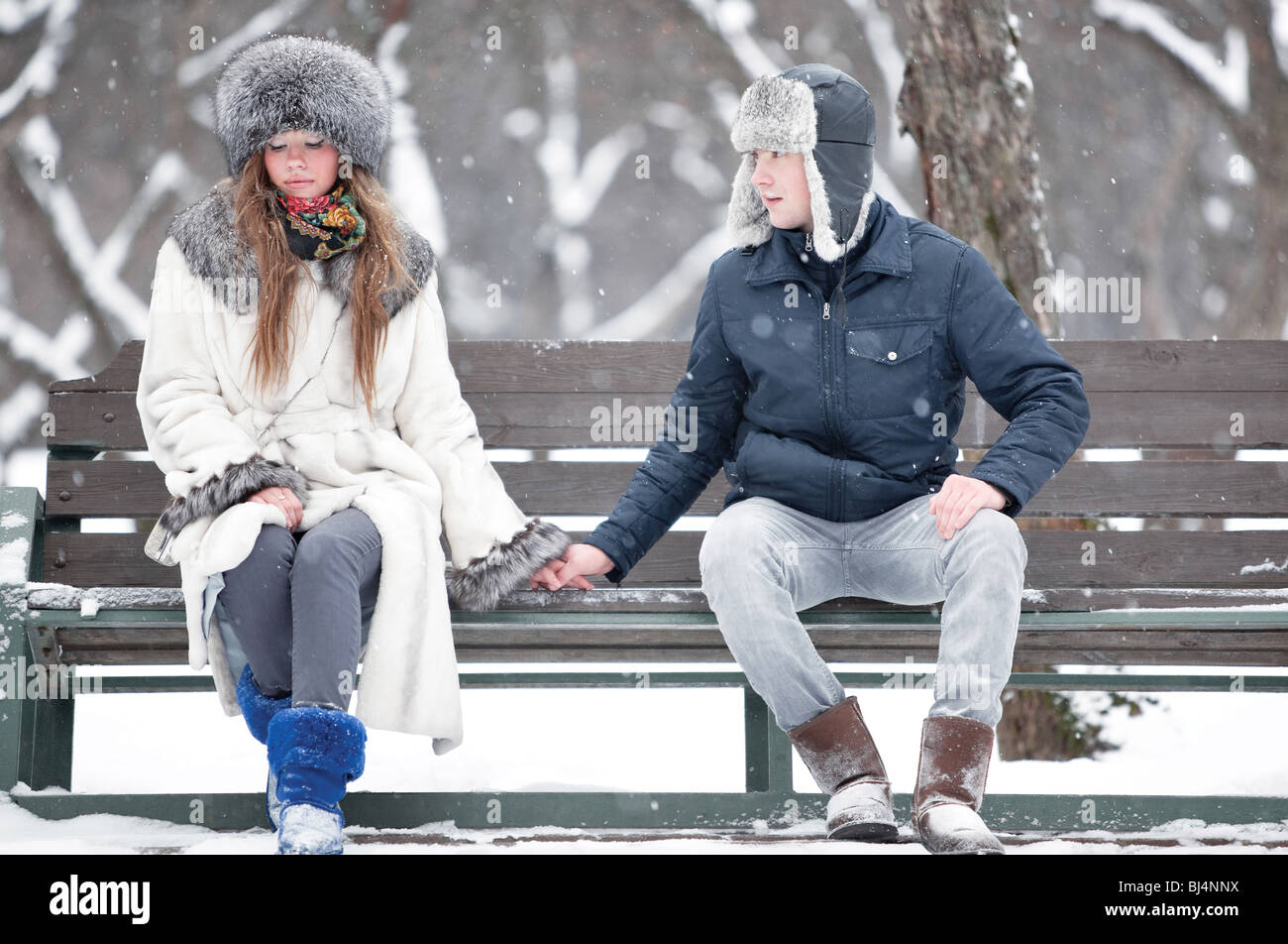Young couple sitting on a bench in a park. - Stock Image
