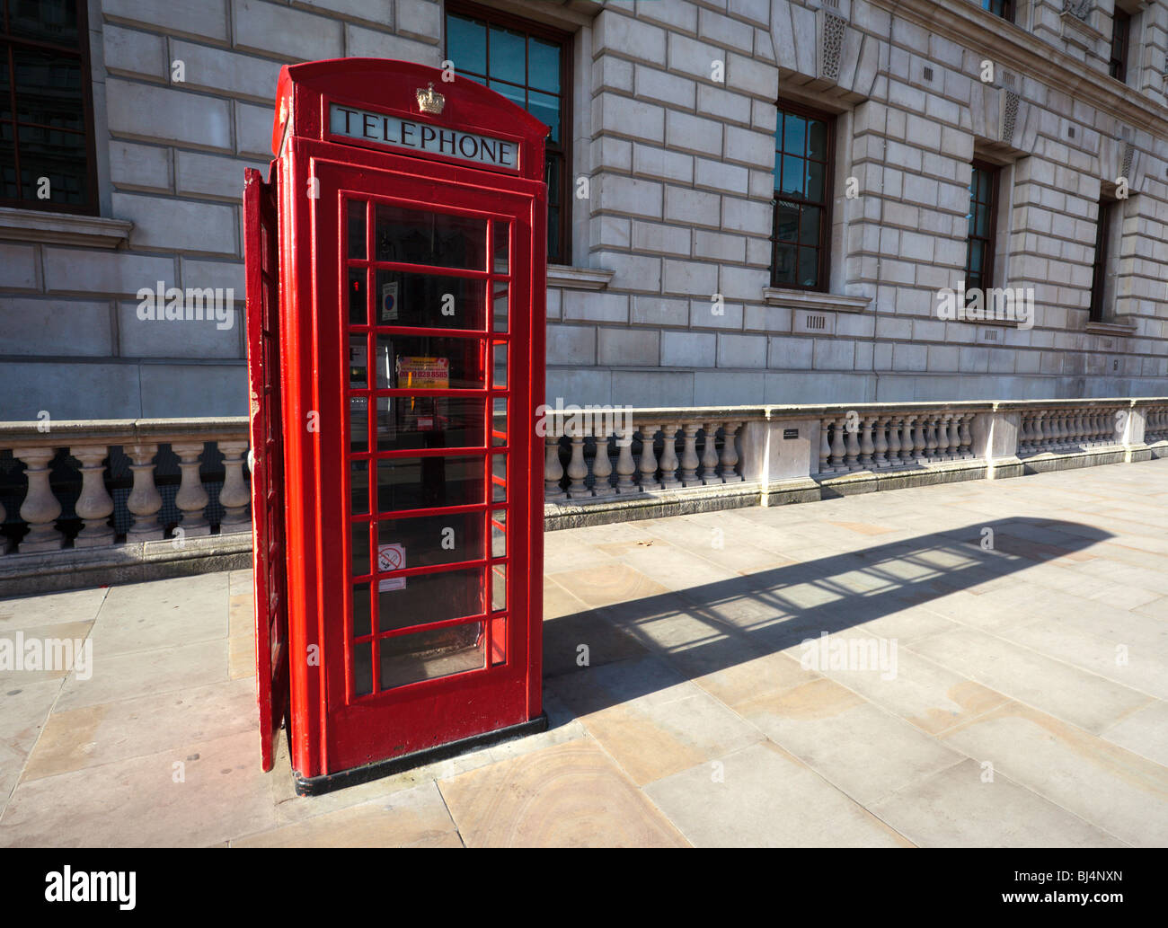 Red Telephone kiosk outside HM Treasury in Parliament Street Westminster London England UK - Stock Image