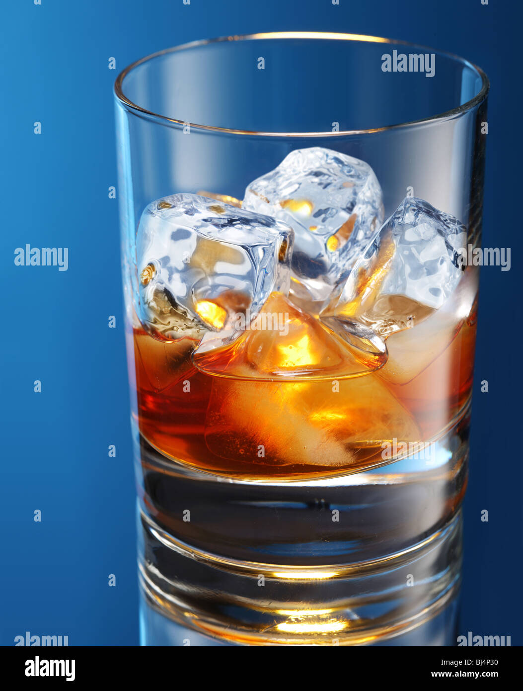 Glass of brandy with ice cubes isolated on a blue - Stock Image