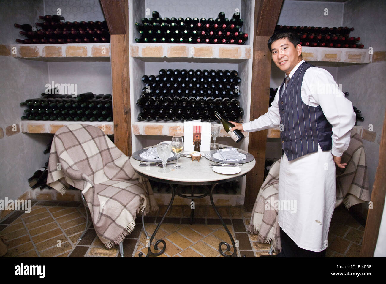 There are a number of unique dining venues, including this one in the wine cellar at Huka Lodge Taupo New Zealand - Stock Image