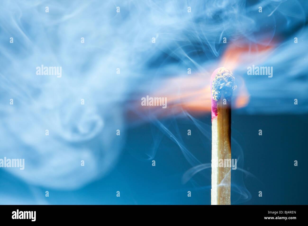 Burning match macro. On blue background. - Stock Image