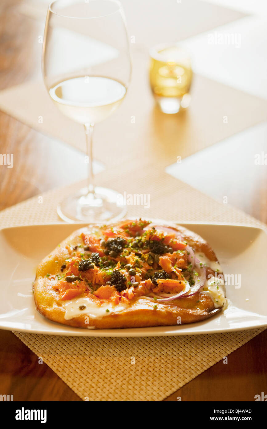 maple-smoked salmon pizza with lemon creme fraiche and a glass of sauvignon blanc wine, Root 246 Restaurant, Solvang, - Stock Image