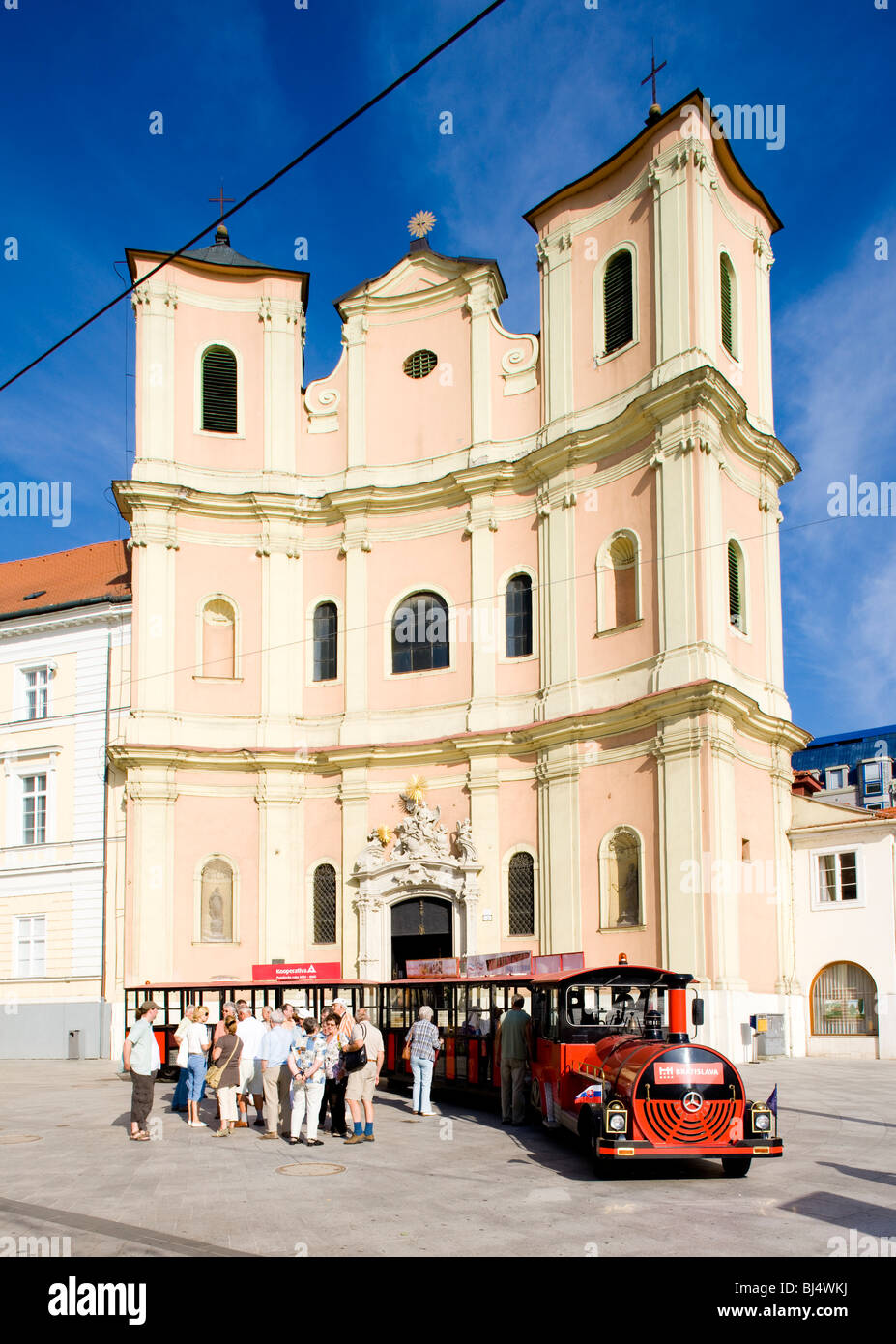 tourist train in front of Trinity Church, Bratislava, Slovakia - Stock Image