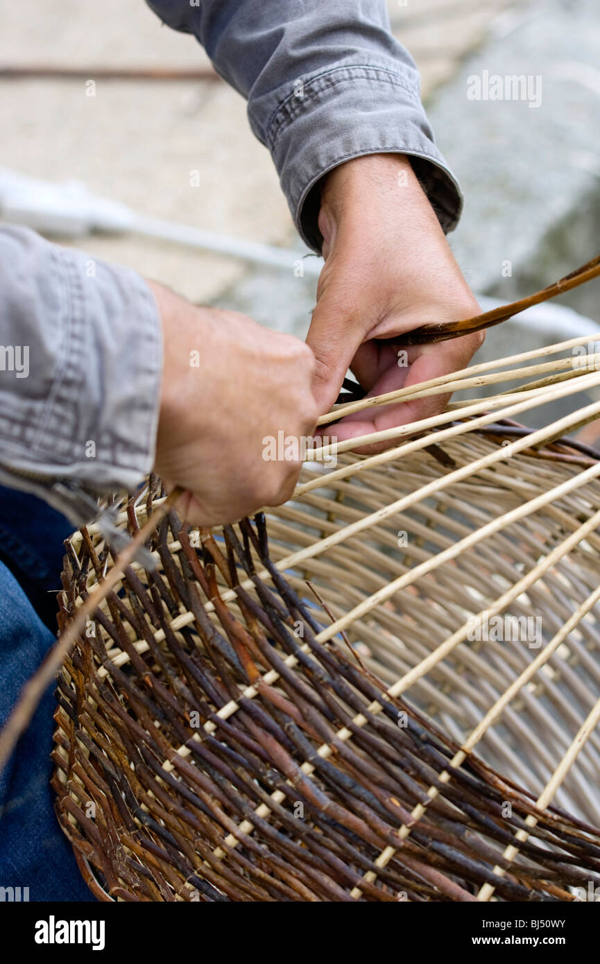 A basket weaver sitting on the street and weaving a basket, Brittany, France, Europe - Stock Image