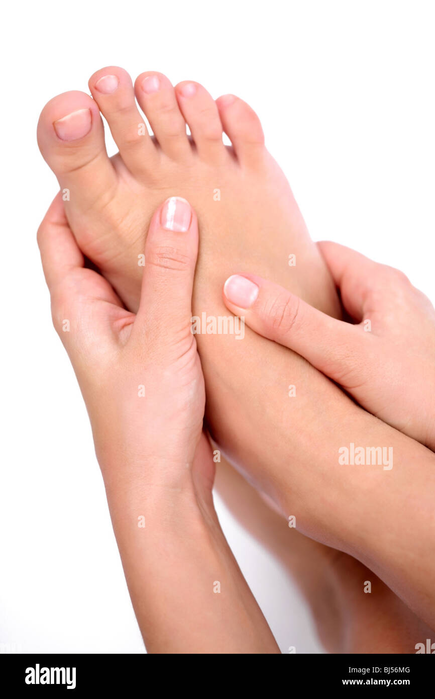 Young woman massages her foot. On a white background. - Stock Image