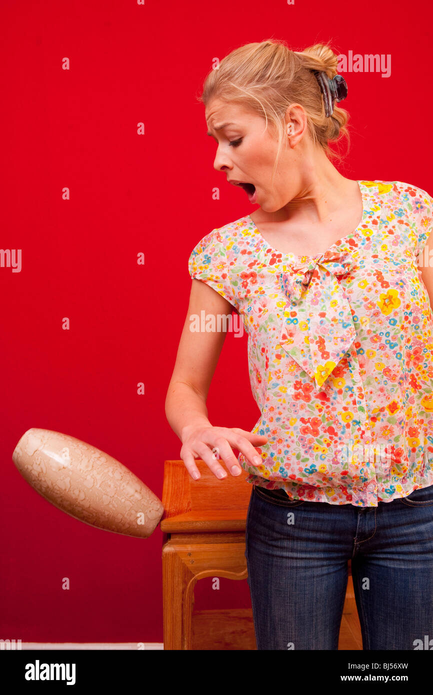 Young woman breaking vase - Stock Image
