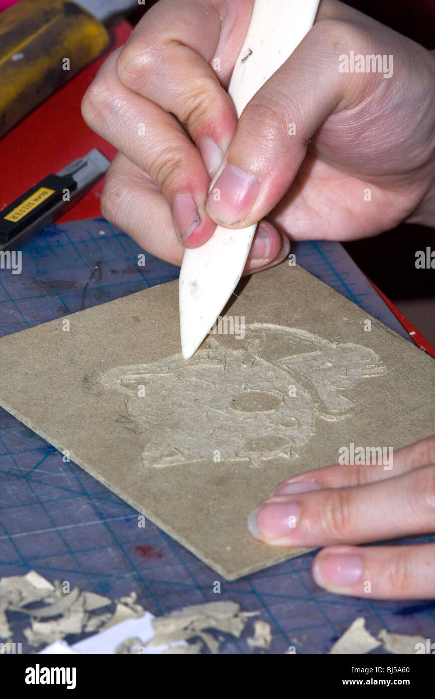 Artist using a Bone Folder to fix an engraving into book board. - Stock Image