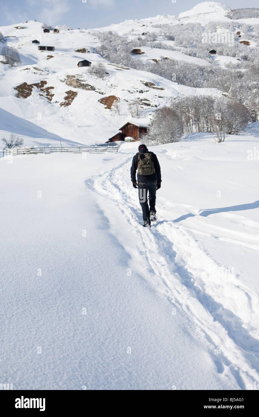Man walking through snow in countryside - Stock Image