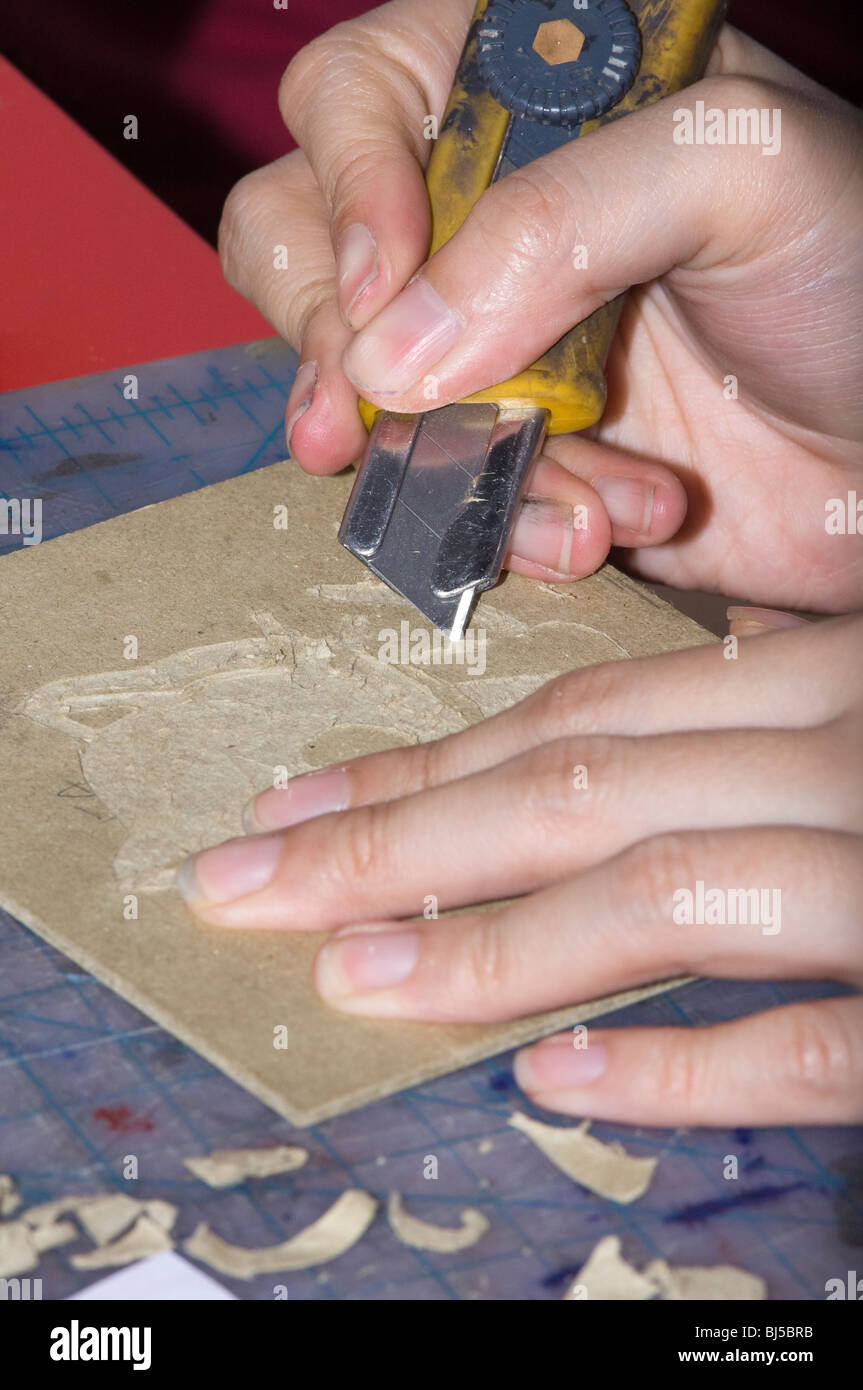 Artist using a Razor Blade Knife to cut an engraving into book board. - Stock Image