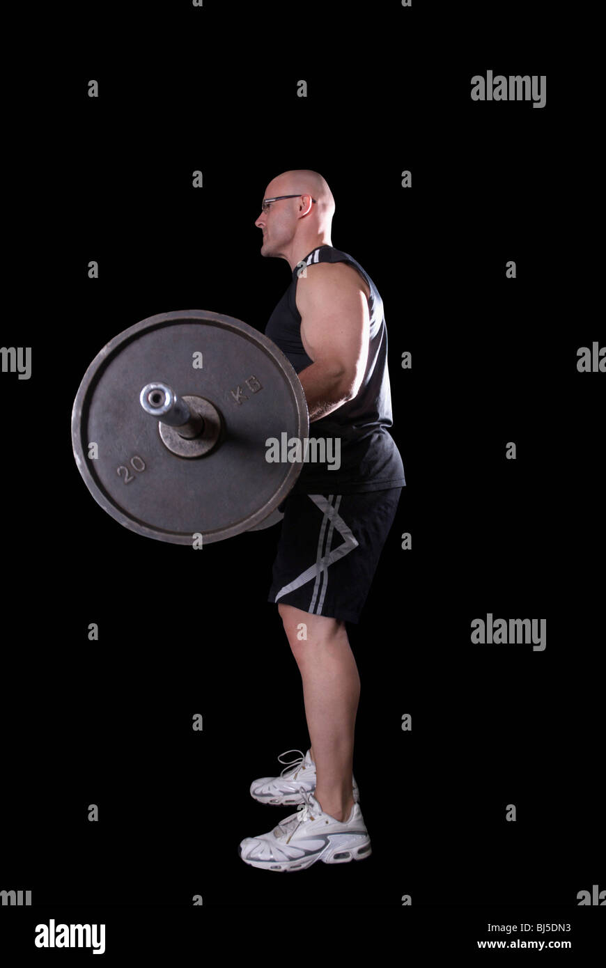 bodybuilder doing biceps curls - Stock Image