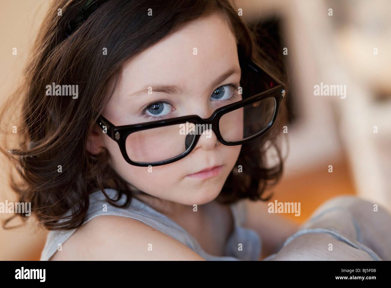 little girl wearing huge pair of glasses - Stock Image
