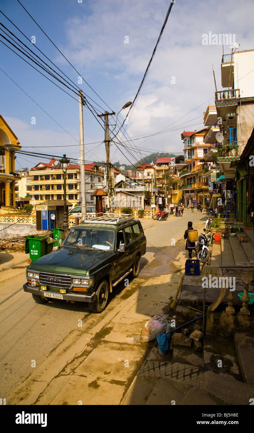 Vietnam, Northern Vietnam, Sapa. 4 wheel drive and hill tribe woman, in a general street scene of Sapa. - Stock Image