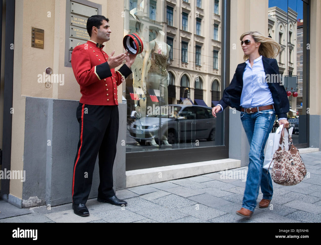 A Turkish bellboy salutes a shopping beautiful young woman in Maximiliastrasse Munich, Germany Stock Photo