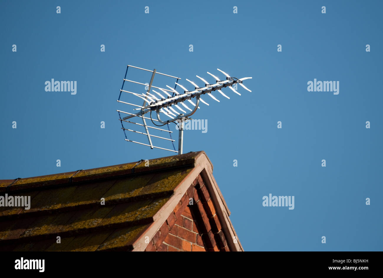 Old fashioned analogue TV aerial on a house roof, Suffolk, UK - Stock Image